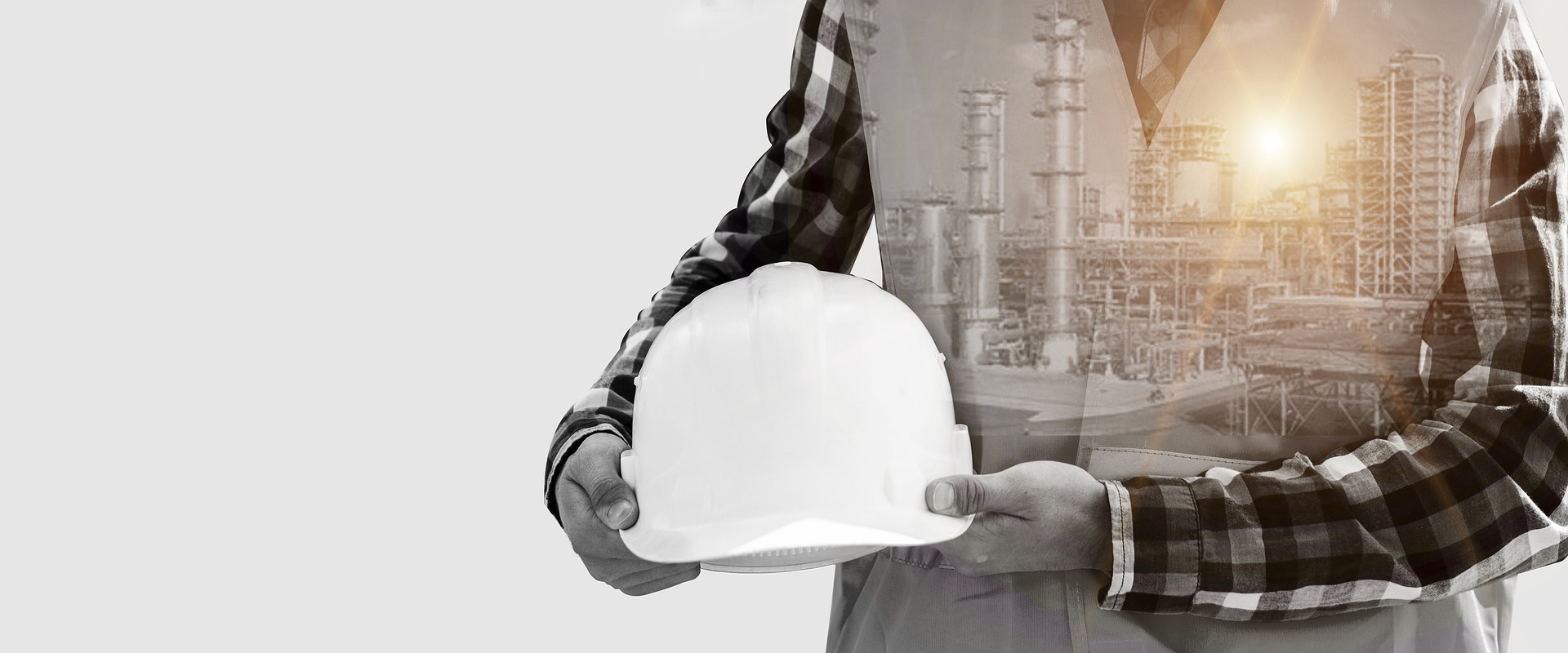 la prévention de l'environnement au sein d'une usine: Photo d'un contremaître tenant son casque et en arrière plan une usine en fonctionnement